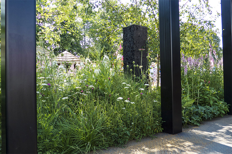 Steel and black coal pillars among native planting at RHS Hampton Court